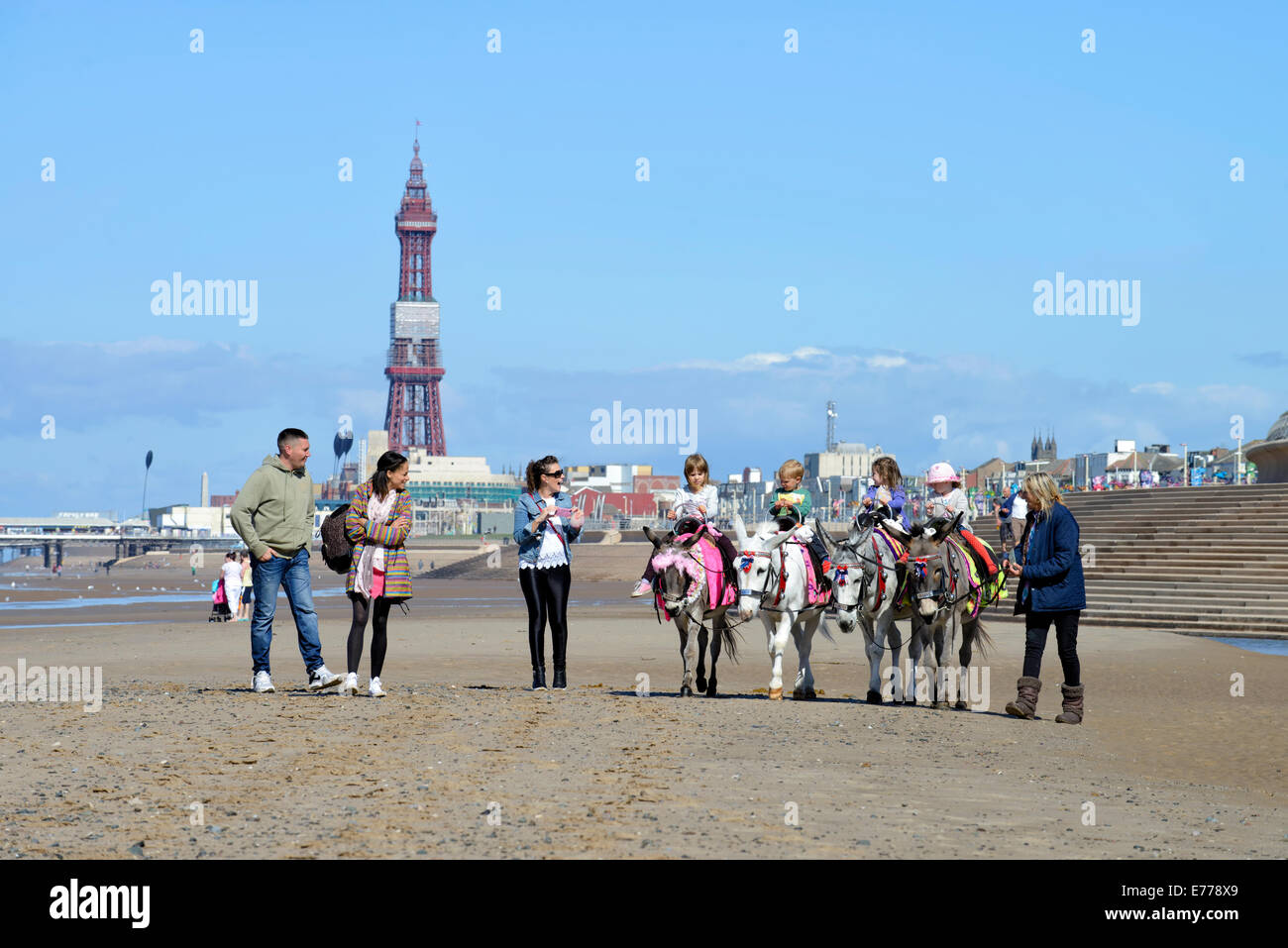 Children enjoying traditional donkey rides on Blackpool beach with iconic Blackpool Tower in the background Stock Photo