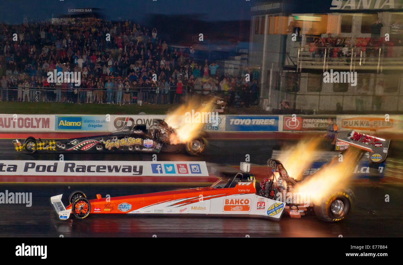 Top Fuel Dragsters racing at night. Driven by Mikael Kagered nearside, Stig Neergaard farside. - Stock Image