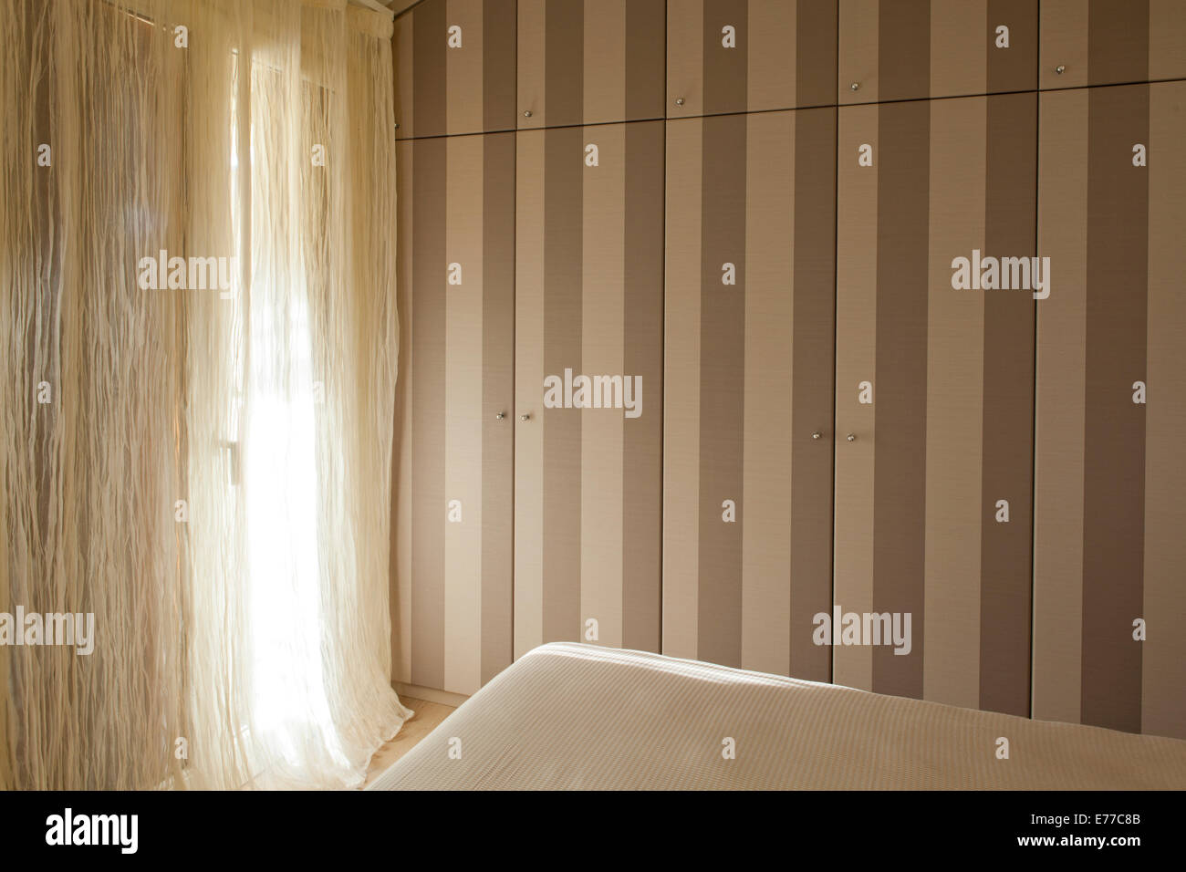 MASTER BEDROOM WARDROBE COVERED WITH STRIPED WALLPAPER - Stock Image