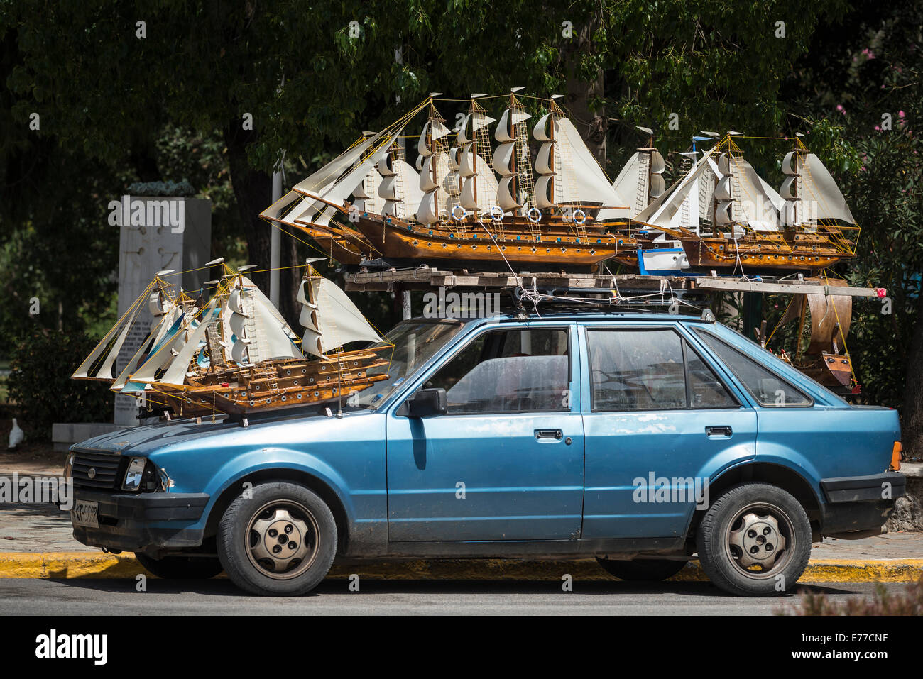 Model sailing ships for sale atop a car in the town of Kalamata, Messenia, Peloponnese, Greece - Stock Image