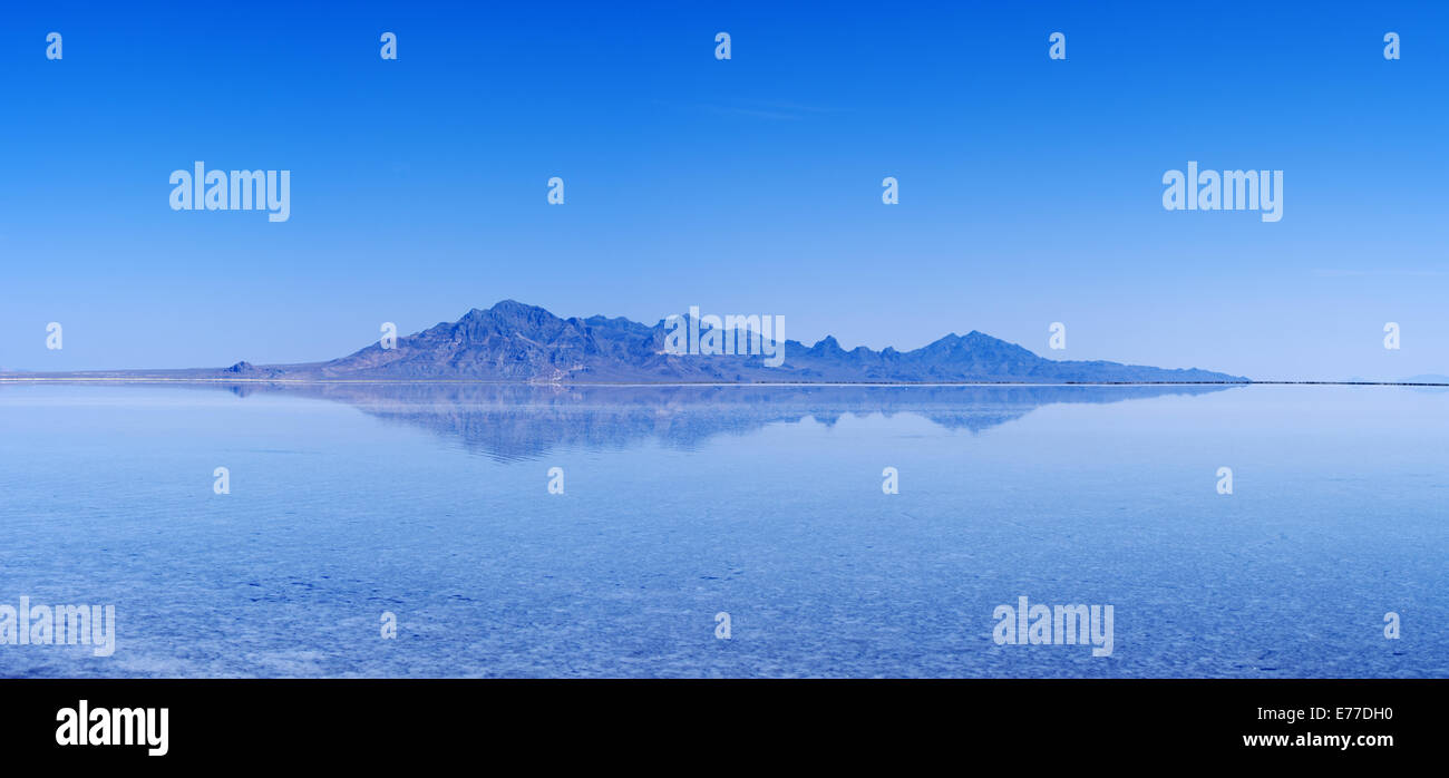 flooded Bonneville Salt Flats with distant mountains and blue sky reflection Stock Photo
