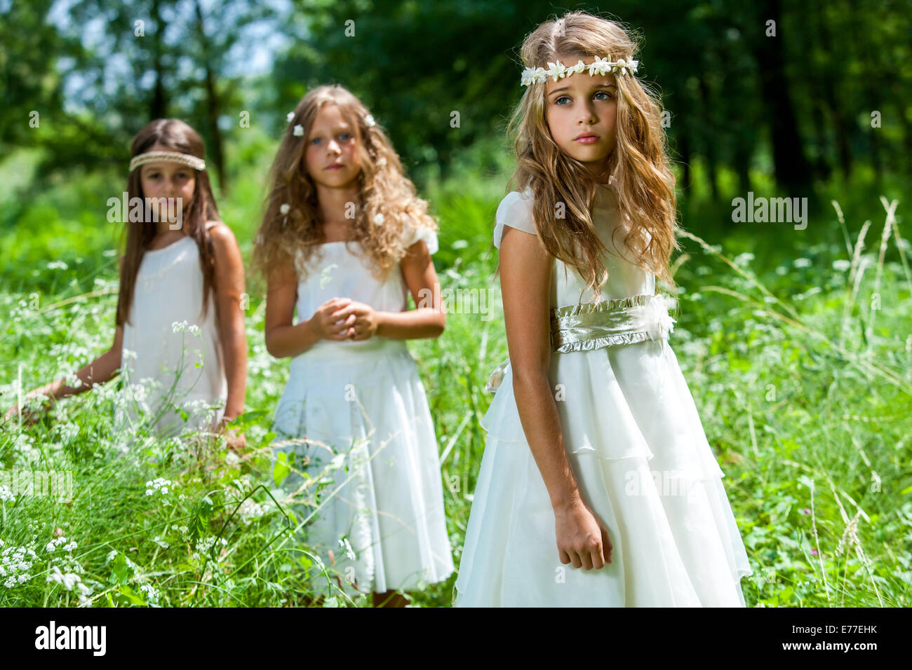 Portrait of three girl friends wearing white dresses in woods. - Stock Image