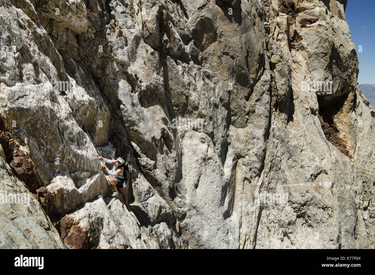 woman climbing up a steep mountain face without a rope - Stock Image