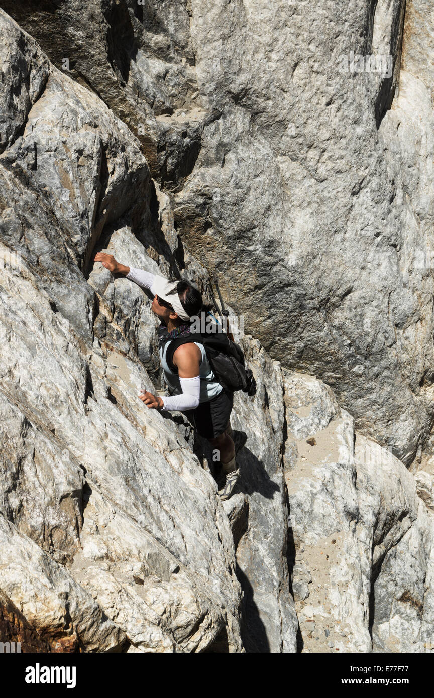 woman climbing up a steep cliff on Laurel Mountain - Stock Image