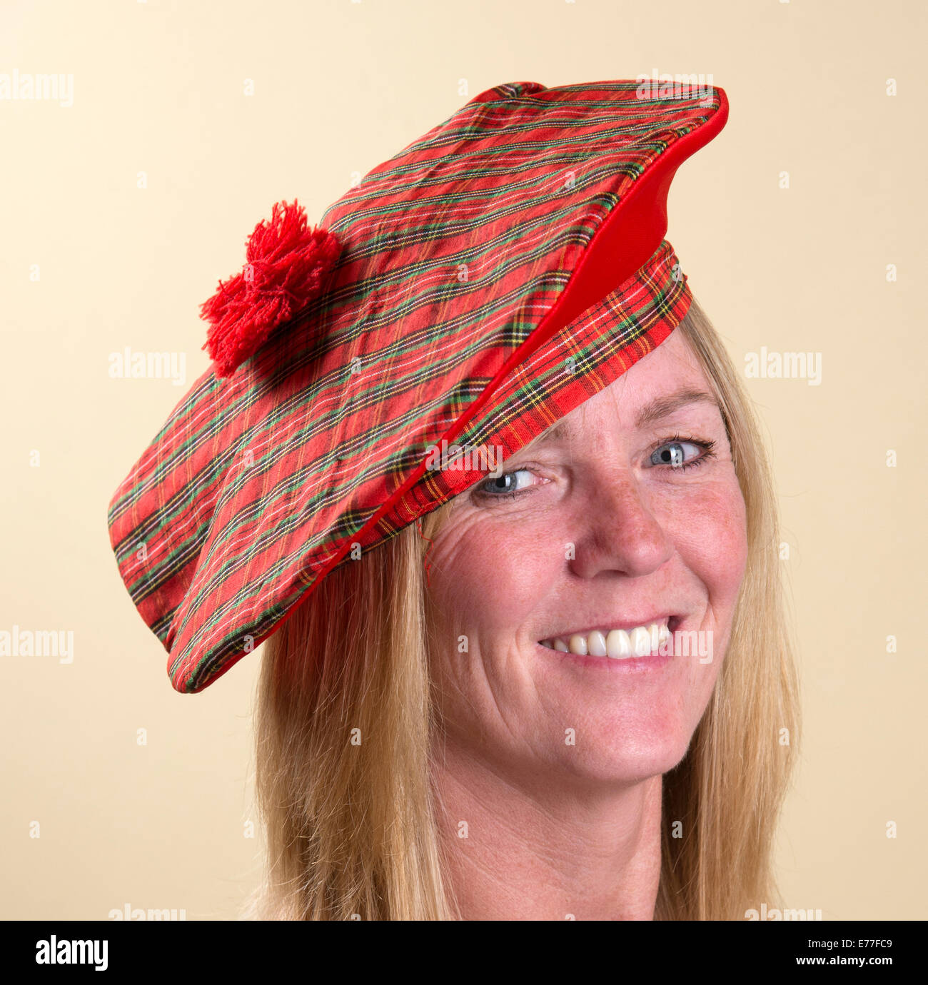 Portrait of a smiling woman wearing a Tam o Shanter Scottish hat - Stock  Image