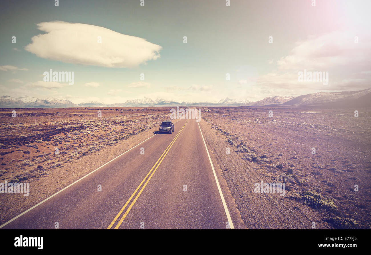 Vintage picture of car on endless country highway, Ruta 40 in Argentina. - Stock Image