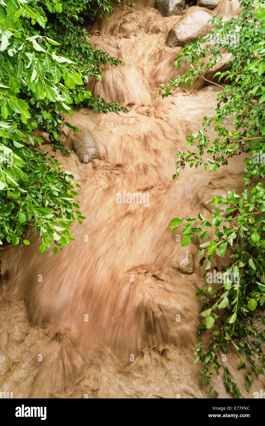 rushing muddy floodwaters in a stream bed with motion blur - Stock Image