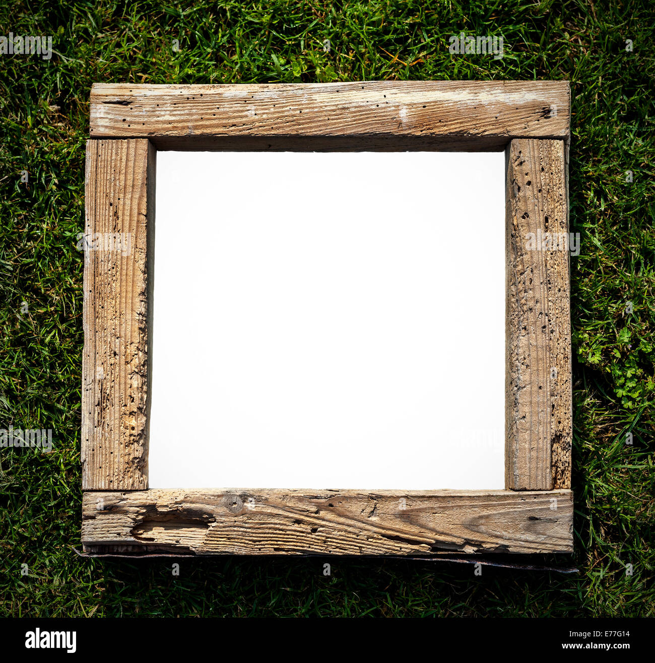 Rustic old grunge wood frame on grass, empty space for text. - Stock Image