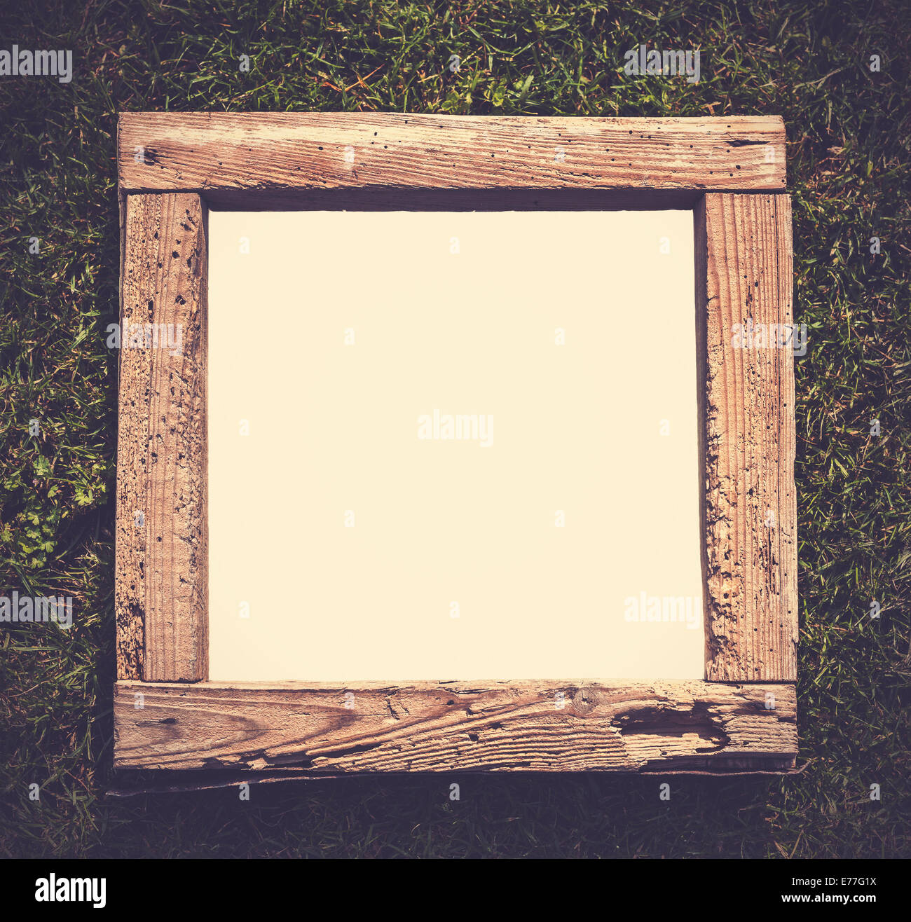 Vintage old grunge wood frame on grass, empty space for text. - Stock Image