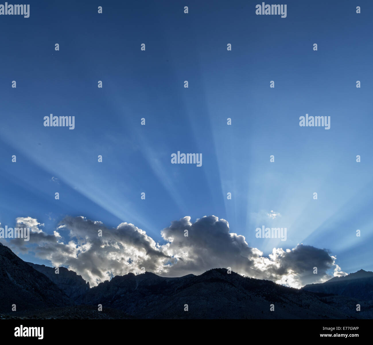 sunrays across a blue sky from behind a cloud over the Sierra Nevada Mountains and Taboose Pass - Stock Image