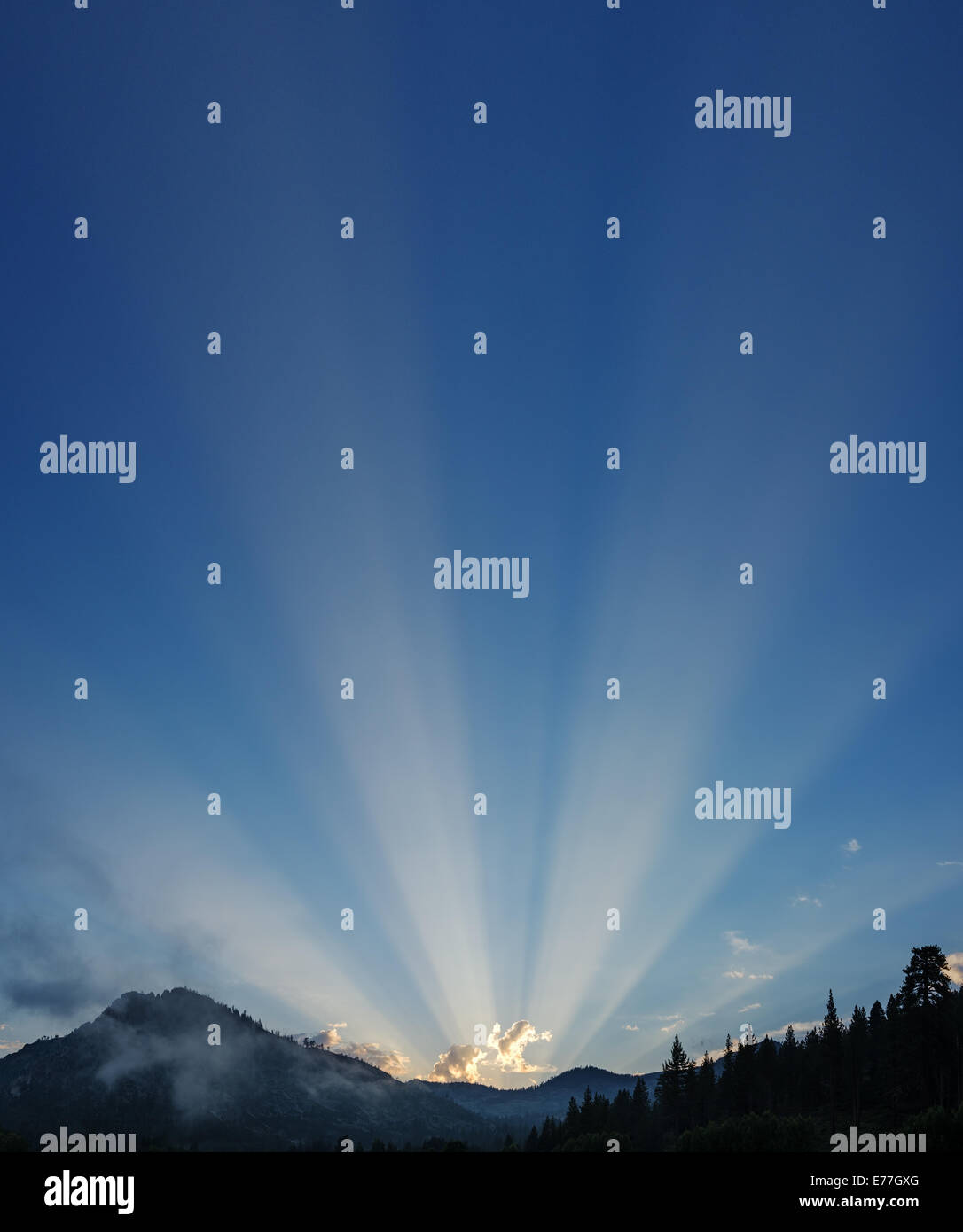 sunrays shine out across the sky over Sierra Nevada mountains - Stock Image