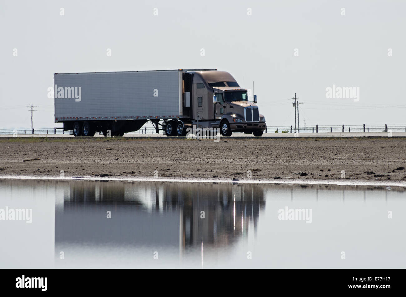 tractor trailer semi  truck driving on a highway causeway with reflection in water - Stock Image