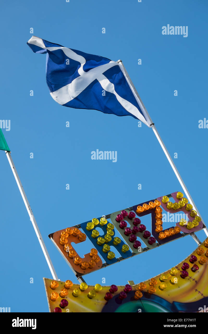 The Saltire, the Scottish national flag flying atop a flagpole above the word crazy written in multi coloured  fairground - Stock Image
