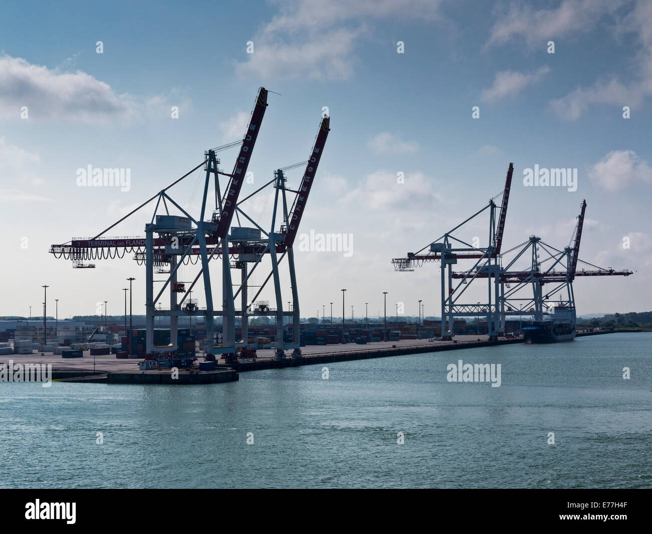 Cranes at the container terminal at Dunkerque (Dunkirk) France. Taken against the light. - Stock Image