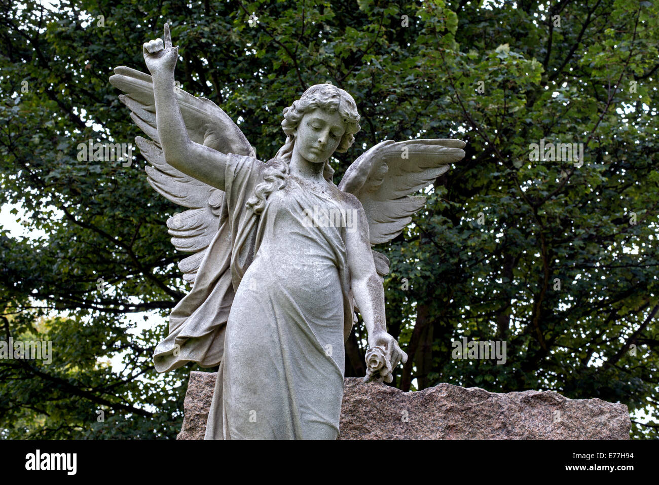 Statue of an angel holding a flower and pointing to heaven in the Grange Cemetery Edinburgh, Scotland. Stock Photo