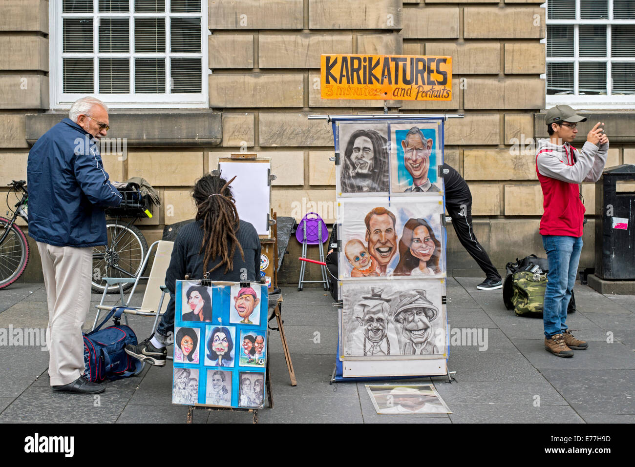 A street artist with examples of his work plies his trade on the High Street in Edinburgh. - Stock Image