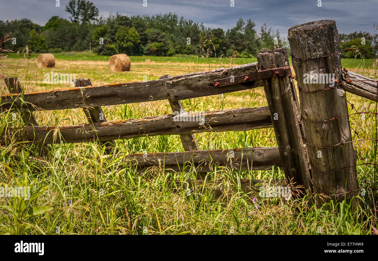 An Old Wood Farm Gate With Hay Bales In The Field Behind
