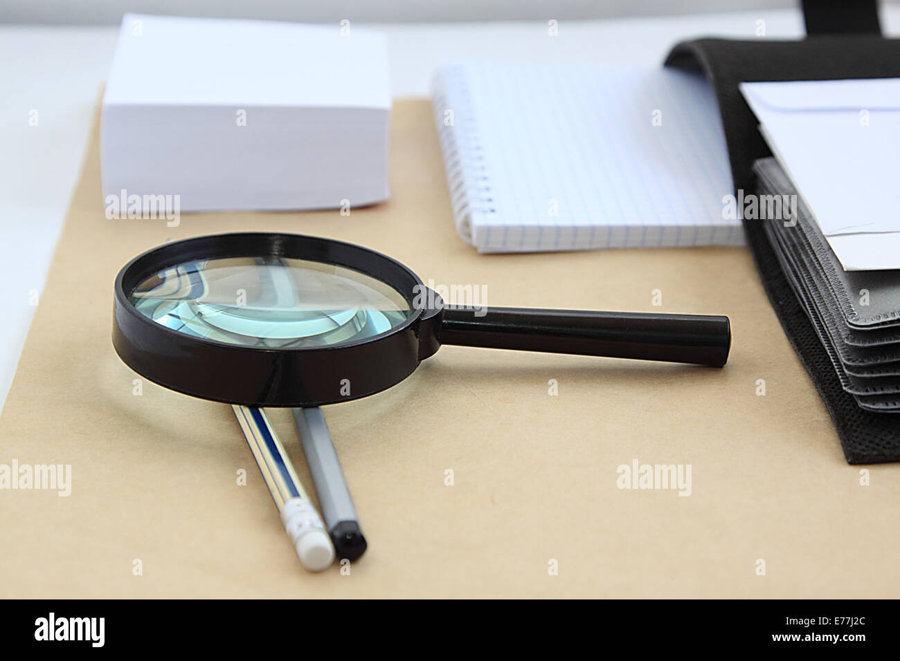Paper notebook and magnifying glass. - Stock Image