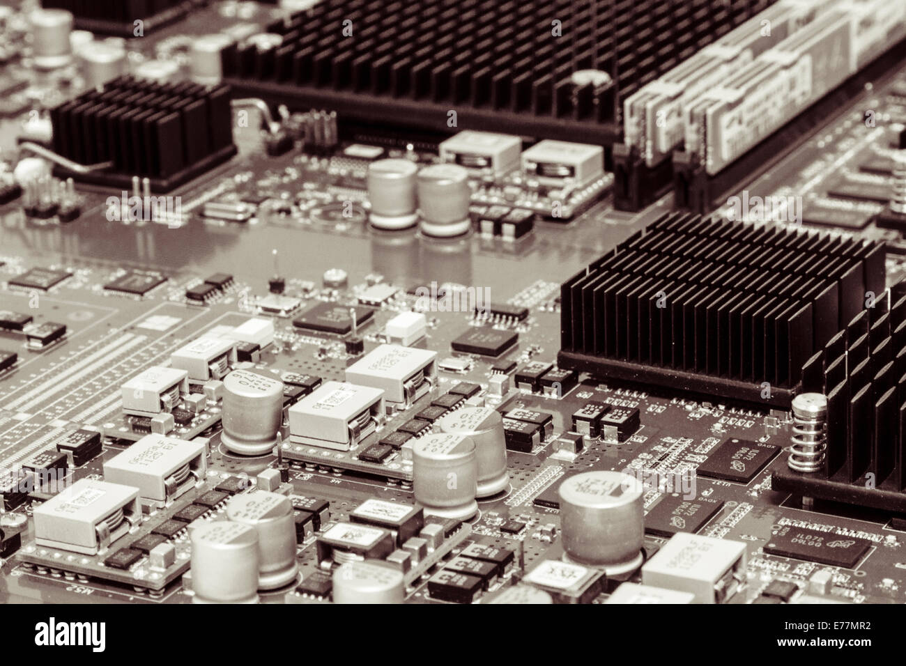 Circuit board of a powerful server computer with chips, capacitors, memory, and heat sinks visible - Stock Image