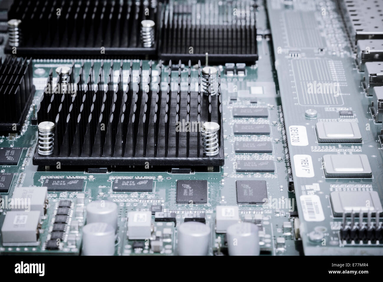 Circuit board of a powerful server computer with chips, capacitors, and heat sinks visible - Stock Image