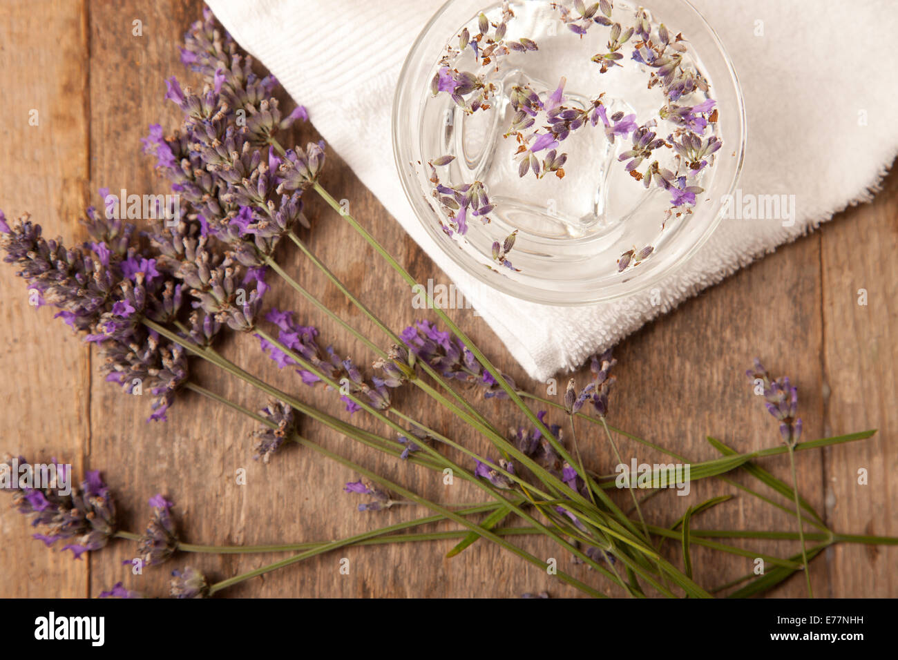 lavenders in the bowl of water on wooden for spa - Stock Image