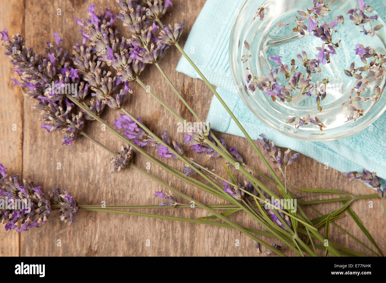 lavenders in water on blue towel on wooden table - Stock Image
