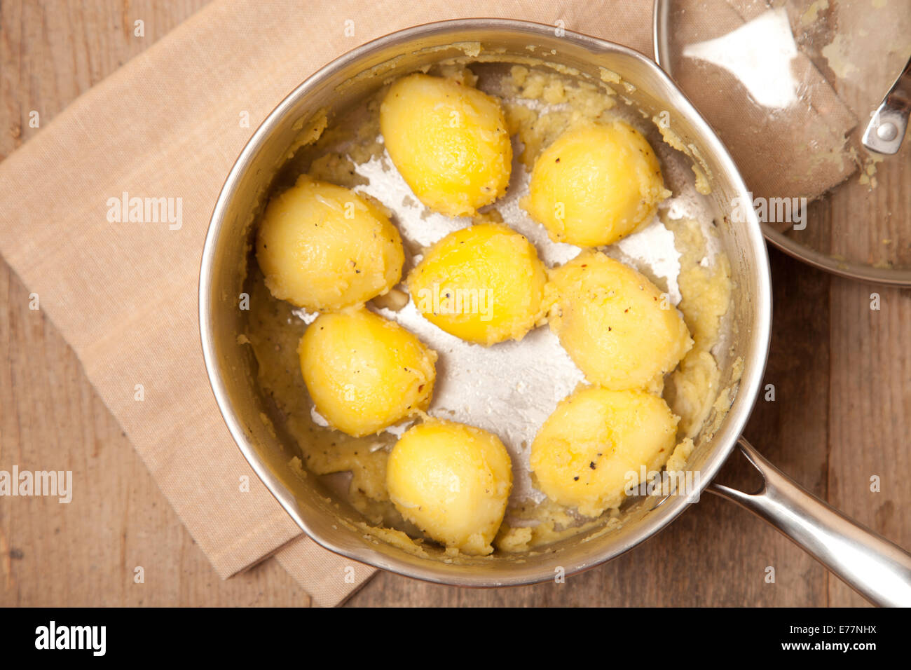 fluff potatoes in saucepan on wooden table - Stock Image