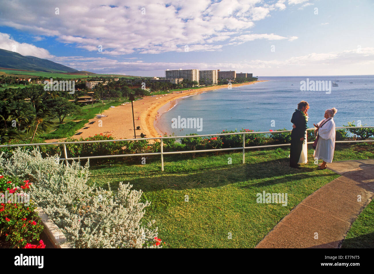 Couple taking their wedding vows above Kaanapali Beach with hotels in distance on Island of Maui in Hawaiian Islands - Stock Image