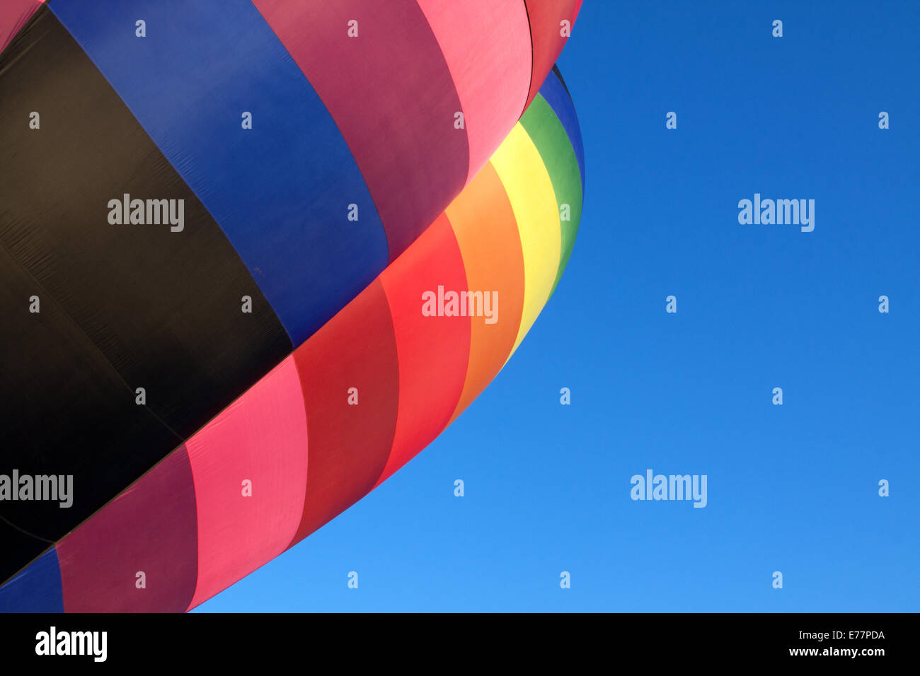 Rainbow-colored hot air balloon angling into view against a clear blue sky Stock Photo