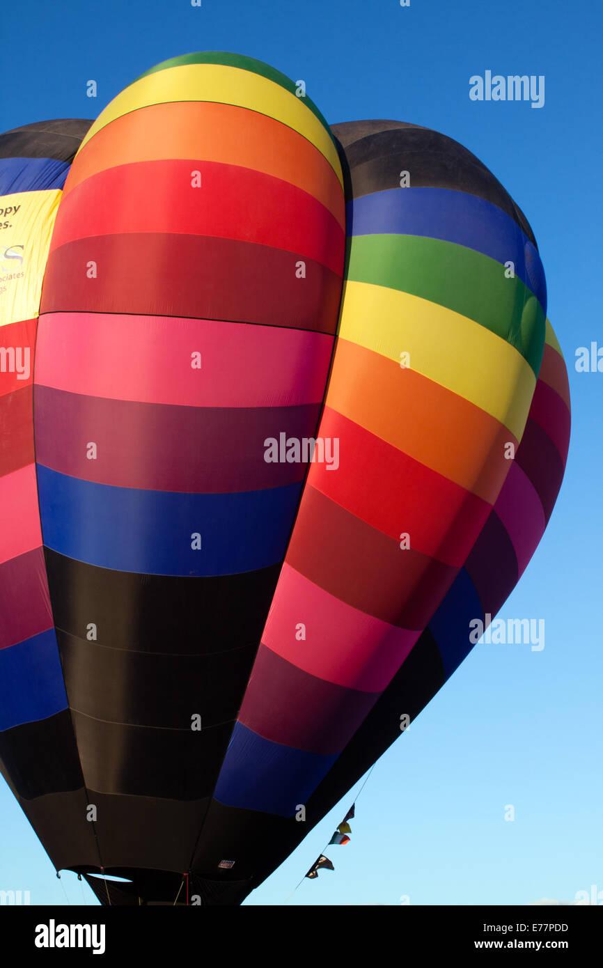 Rainbow-colored hot air balloon against a blue sky Stock Photo