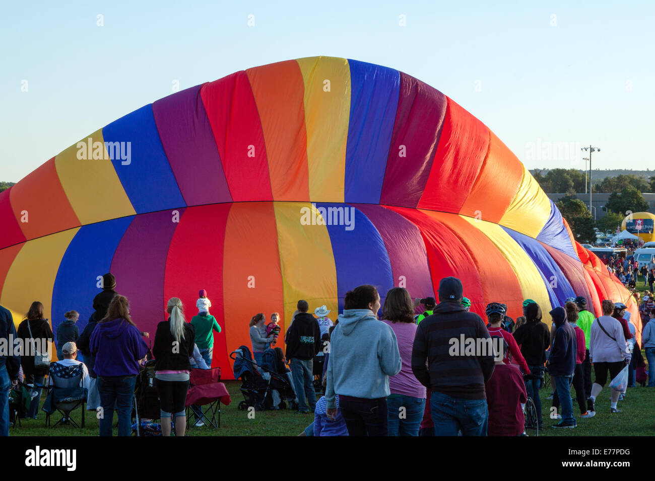 A crowd watches as a rainbow colored hot air balloon is inflated in Colorado Springs, CO Stock Photo