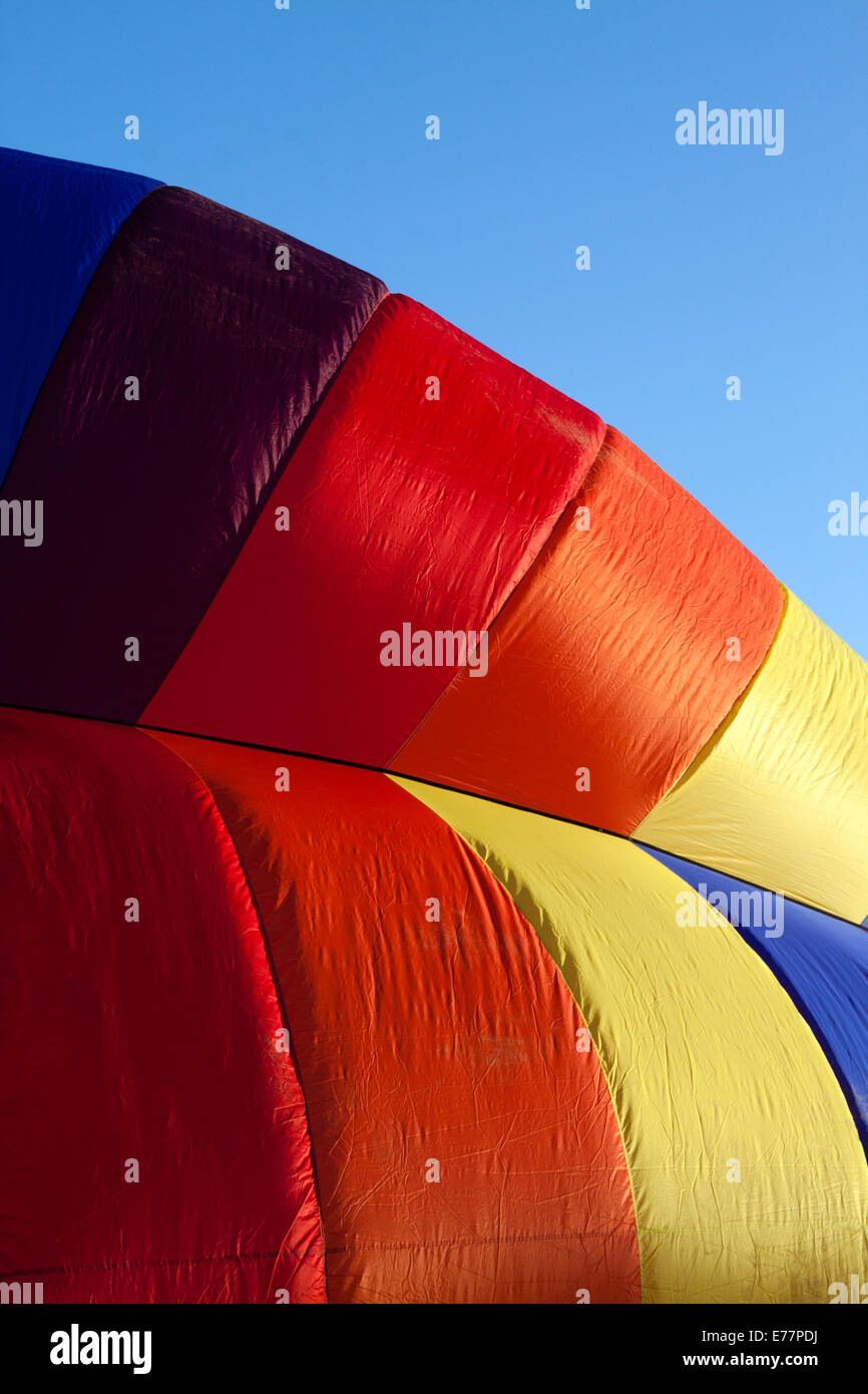 Detail of a hot-air balloon being inflated in early morning light against a blue sky Stock Photo