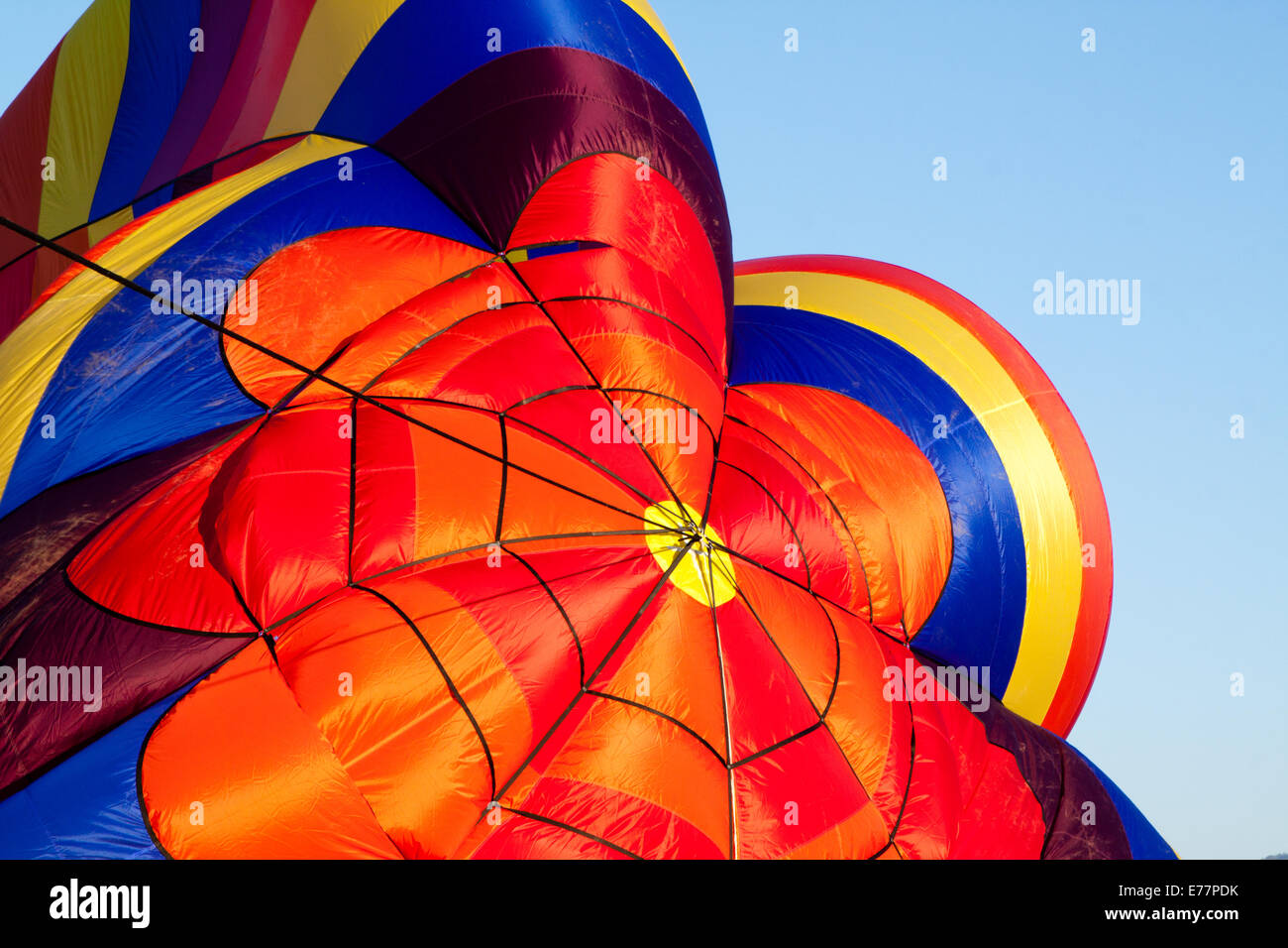 Top of a partially inflated rainbow-colored hot-air balloon Stock Photo