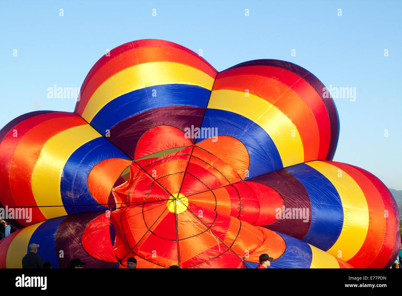 Top of canopy of a partially inflated hot air balloon against a blue sky Stock Photo