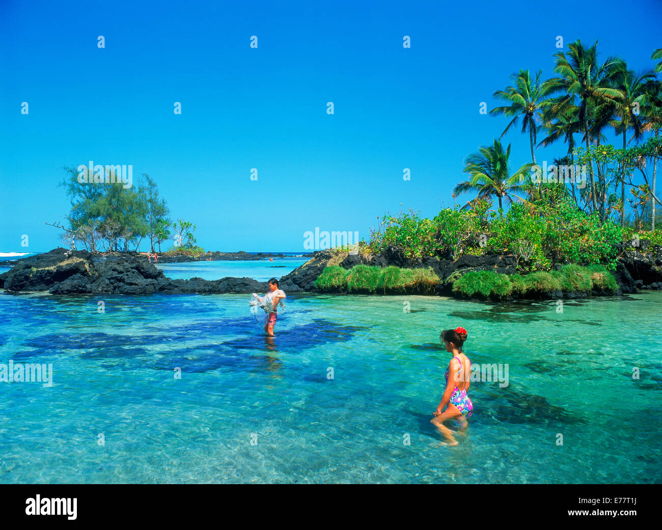 hawaiian girl and boy in clear lagoon waters near hilo on the big
