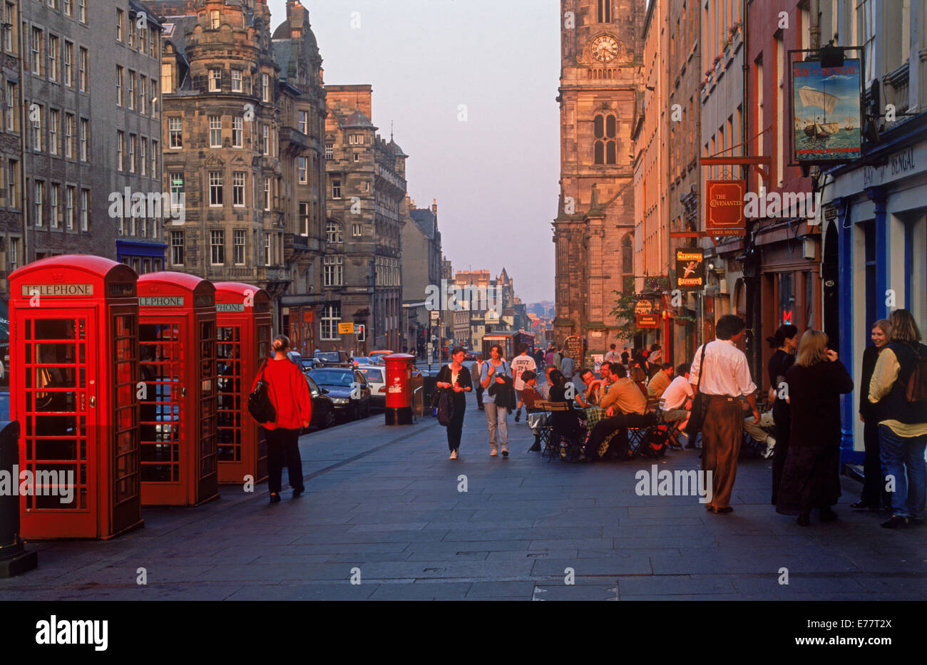 Telephone booths, pedestrians and pubs along The Royal Mile in Edinburgh in sunset light - Stock Image