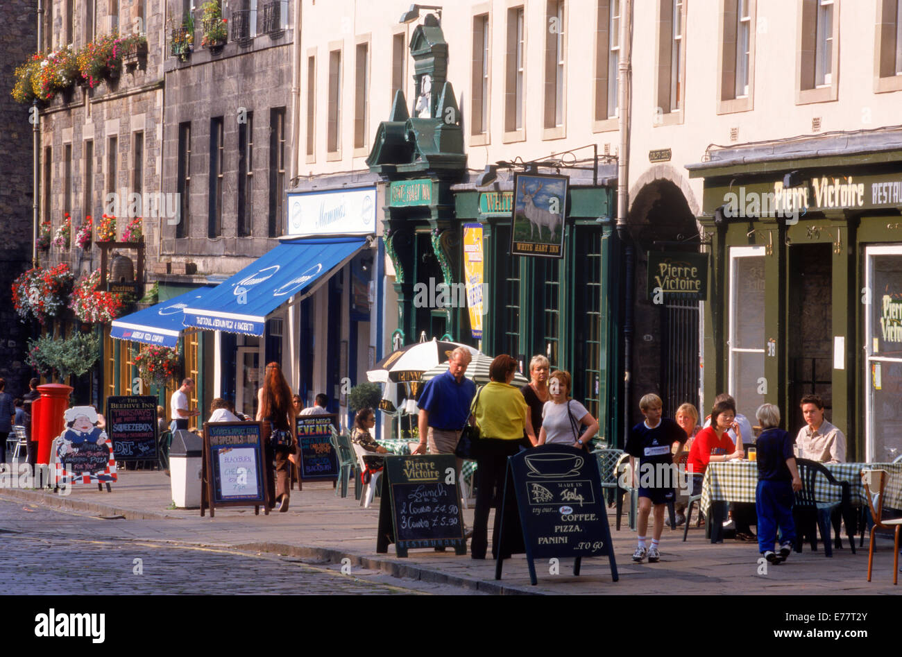 People at sidewalk tables at old pubs along Grassmarket in Edinburgh Scotland - Stock Image
