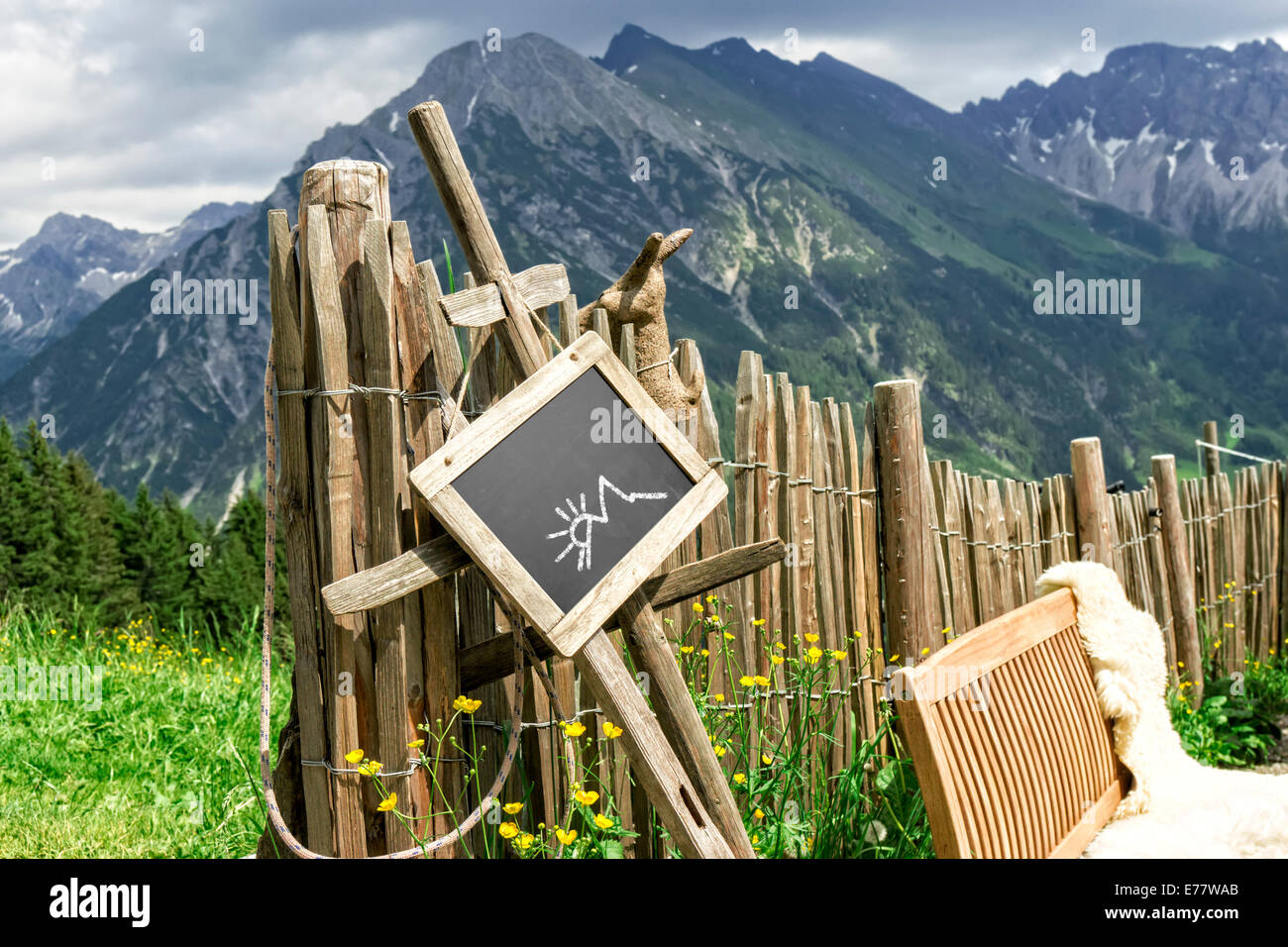 Wooden palisade with chalkboard hint panel and lambskin coated bench in front of Chalkboard with empty - Stock Image