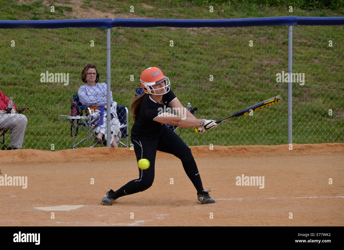 Hitting a foul ball in a high school softball game - Stock Image