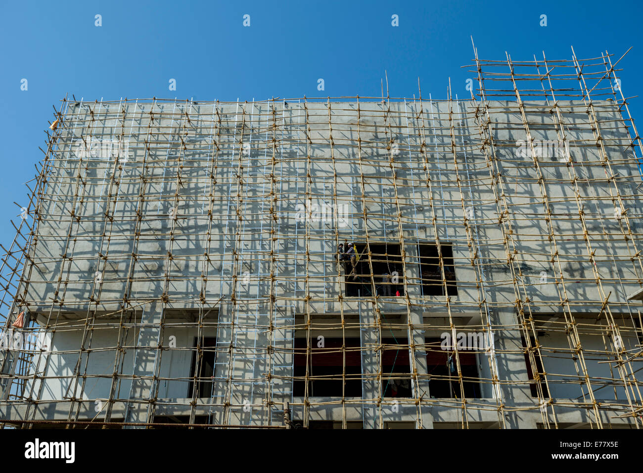 A construction site of a new concrete building with bamboo scaffolding attached, Ahmedabad, Gujarat, India - Stock Image