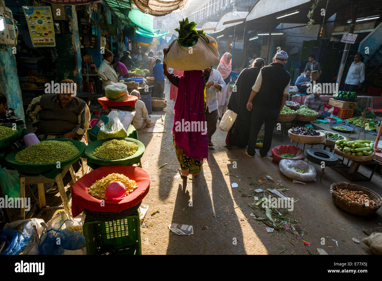 A woman is carrying a bag with vegetables on her head through the vegetable market, Ahmedabad, Gujarat, India - Stock Image