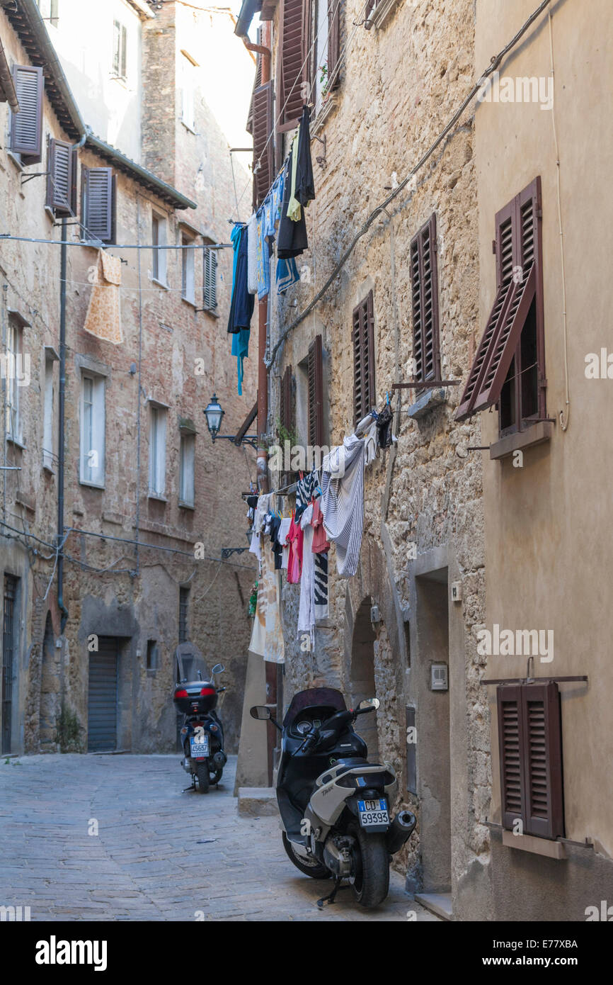An alley in the city of Volterra in Tuscany in Italy with laundry hanging outside the windows and motor cycles - Stock Image