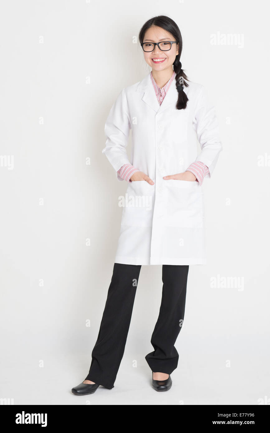 Portrait Of Asian Chinese Girl In White Lab Uniform Smiling Full Body Standing On Plain Background