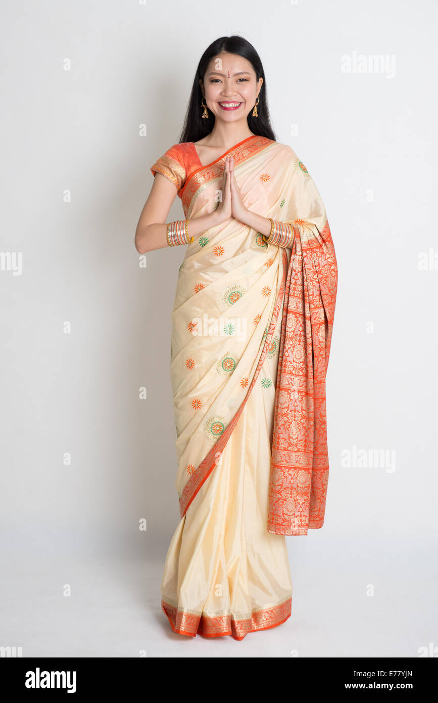Asian Indian girl in a greeting pose, traditional sari costume, full length standing on plain background - Stock Image