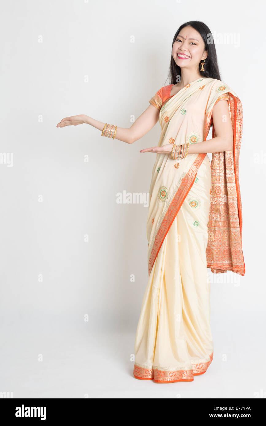 Full length Asian Indian girl hands showing something on plain background. - Stock Image
