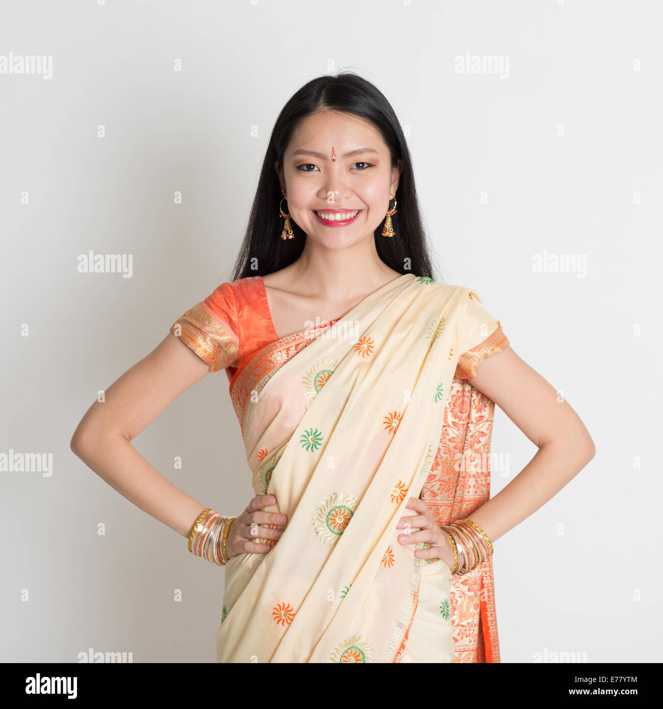 Portrait of confident Indian girl in sari smiling over grey background. - Stock Image