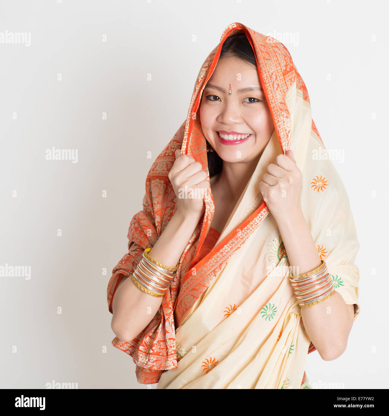 Portrait of Indian Muslim girl in sari covered her head, smiling confidently on grey background. - Stock Image