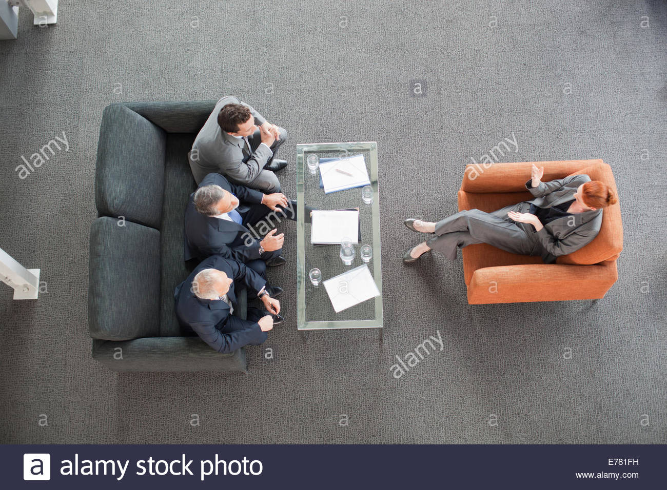 Businesswoman leading meeting with co-workers in lobby - Stock Image