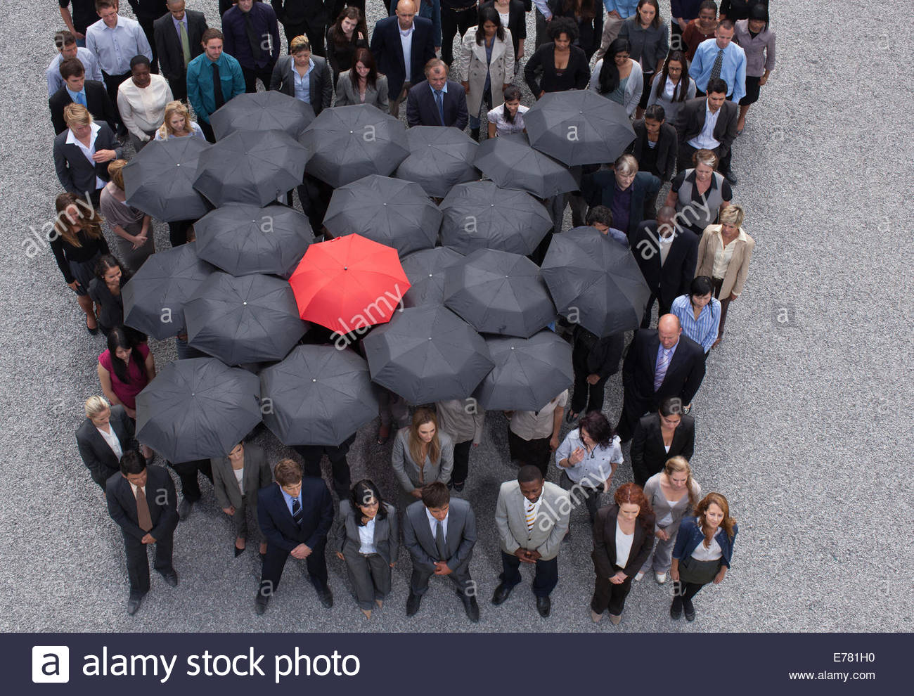 Umbrella at center of circle formed by business people - Stock Image