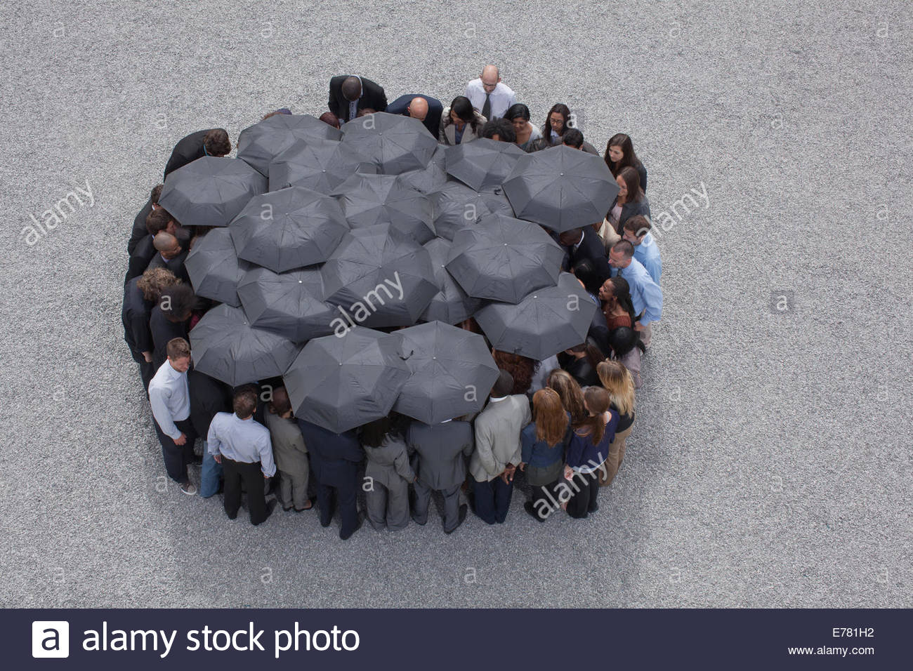 Circle formed by business people with umbrellas - Stock Image